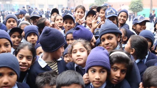 Group of kids in school uniform smiling and waving to the camera during class break