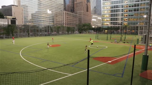 A group of kids play baseball on a field in Battery City downtown Manhattan New York New York on June 24th 2015 Shots Wide shot pans down from the...