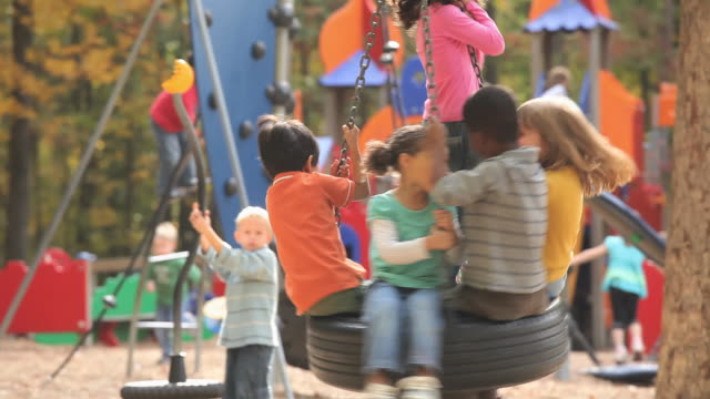 ms tu td group of kids (2-7) playing on playground tire swing / richmond, virginia, usa. - parco giochi video stock e b–roll