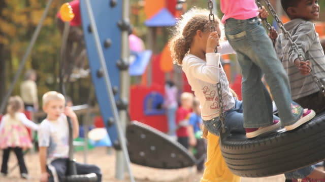 ms tu td group of kids (4-7) playing on playground tire swing / richmond, virginia, usa. - tyre swing stock videos & royalty-free footage