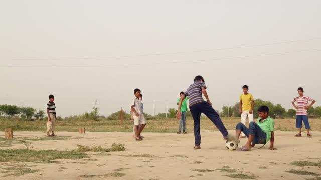 vidéos et rushes de group of kids playing soccer, haryana, india - adolescence