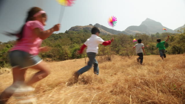 Group of kids playing with paper windmill in the forest