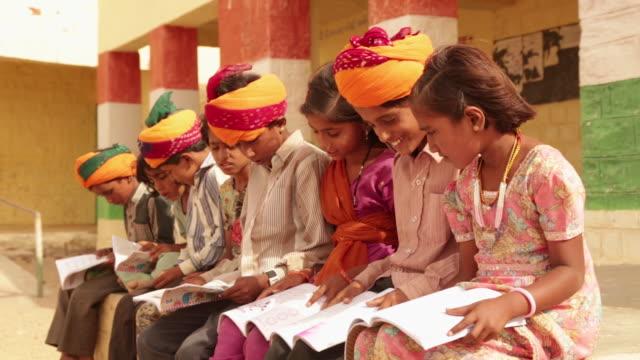 vídeos de stock e filmes b-roll de group of kids reading a book in a school, jaisalmer, rajasthan, india - pobreza questão social