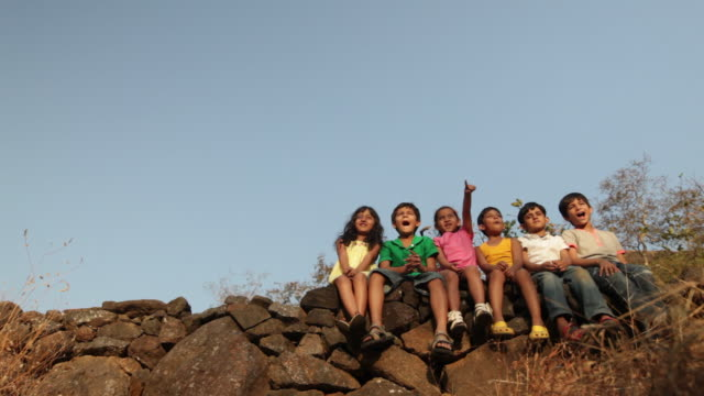 group of kids sitting on rock in the forest - newoutdoors stock videos & royalty-free footage