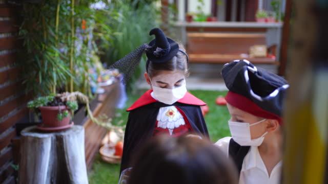 stockvideo's en b-roll-footage met groep kinderen truc of behandelen tijdens covid-19 pandemie het dragen van gezichtsmaskers - graaf dracula