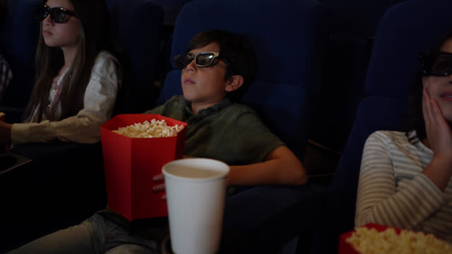 vídeos de stock, filmes e b-roll de grupo de miúdos que prestam atenção a um filme 3d no cinema ao apreciar petiscos - óculos de terceira dimensão