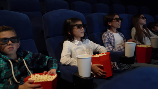 映画館で怖い3d映画を見ている子供たちのグループ - 3dメガネ点の映像素材/bロール