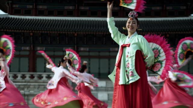 ms group of korean fan dance group performing behind gyeongbokgung palace / seoul, south korea  - 韓国文化点の映像素材/bロール