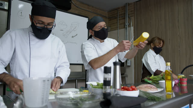 vídeos de stock e filmes b-roll de group of latin american chefs teaching a cooking class during the covid-19 pandemic all wearing protective face masks - latin american and hispanic ethnicity