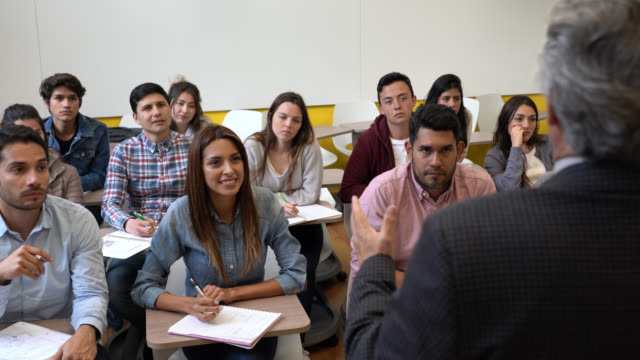 Group of latin american students looking very engaged paying attention to the teacher laughing and raising hands