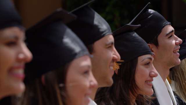 group of latin american students standing in a row at their graduation ceremony outside looking very happy - mortar board stock videos and b-roll footage