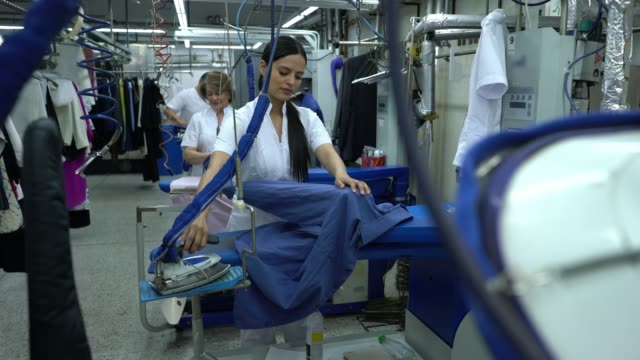 group of latin american workers at an industrial laundry service ironing clothes - lavanderia pubblica video stock e b–roll