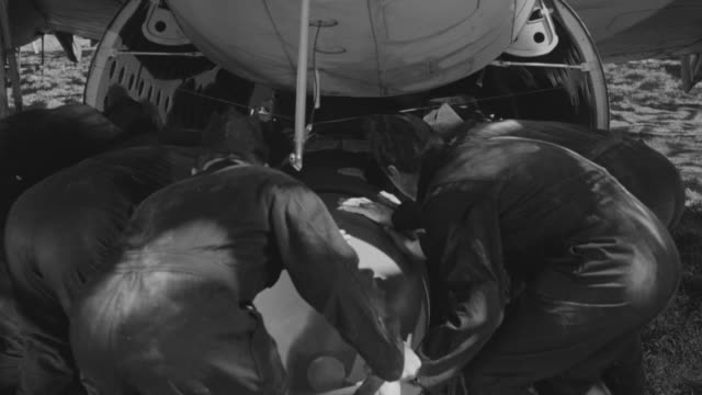 ms group of loading large bomb onto an airplane from bottom - portello video stock e b–roll