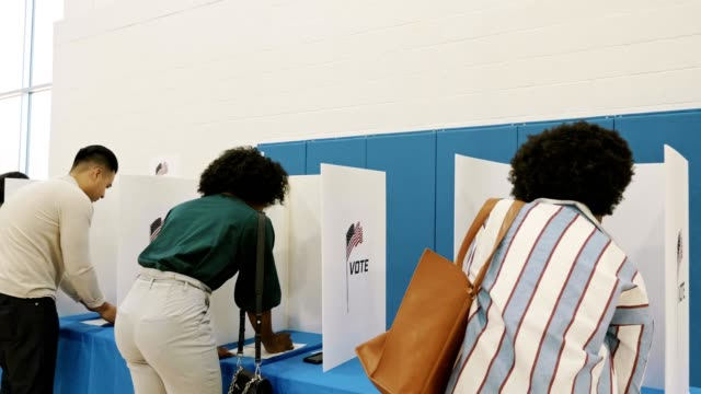 group of male and female voters voting in polling place on election day - voting ballot stock videos & royalty-free footage