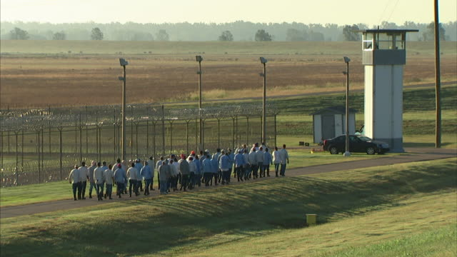 group of male criminal prisoners walking in group on asphalt road outside maximum security prison fencing toward guard tower incarceration not jail... - prisoner stock videos & royalty-free footage