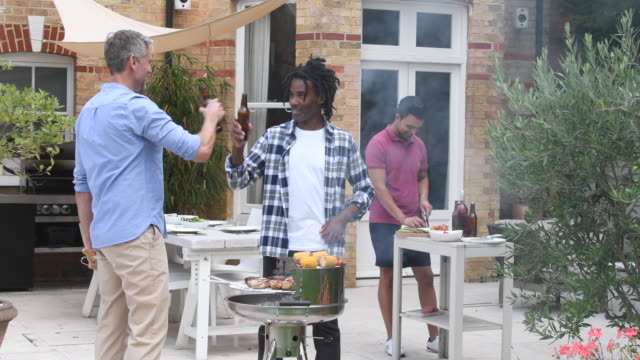 Group of male friends enjoying beer and cooking food on bbq