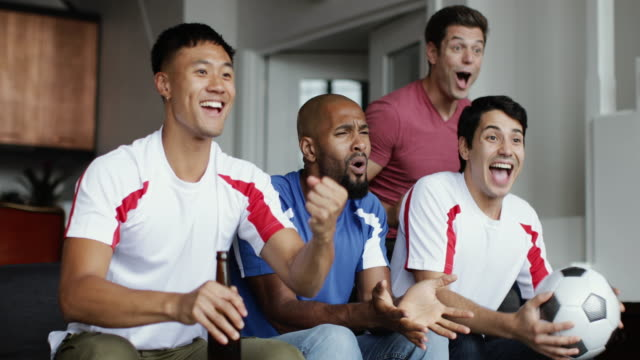 Group of male friends watching a football match