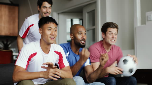 group of male friends watching a football match - four people stock videos & royalty-free footage