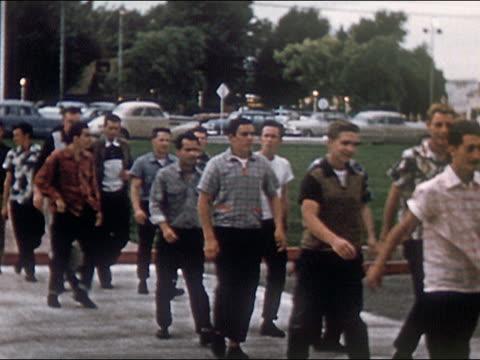 1954 group of male high school students walking down sidewalk / southern California