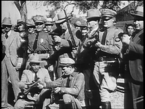 b/w 1934 group of male law enforcement officers pursuing dillinger loading guns / tucson az - john dillinger stock-videos und b-roll-filmmaterial