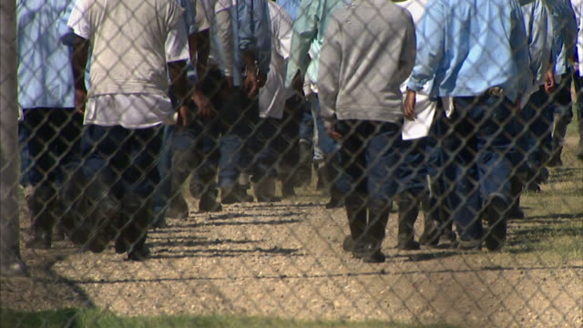 group of male prisoners on other side of fence walking up dirt and grass path. incarceration, prison, not jail, work detail, the farm. - 囚人点の映像素材/bロール