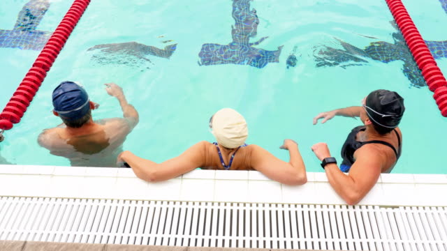 MS HA Group of mature athletes resting between sets during early morning workout in outdoor pool