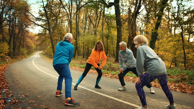 group of mature folks exercising in a forest. - active seniors stock videos & royalty-free footage