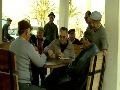 vídeos y material grabado en eventos de stock de group of mature portuguese men wearing flat caps play cards on table out doors. - carta naipe