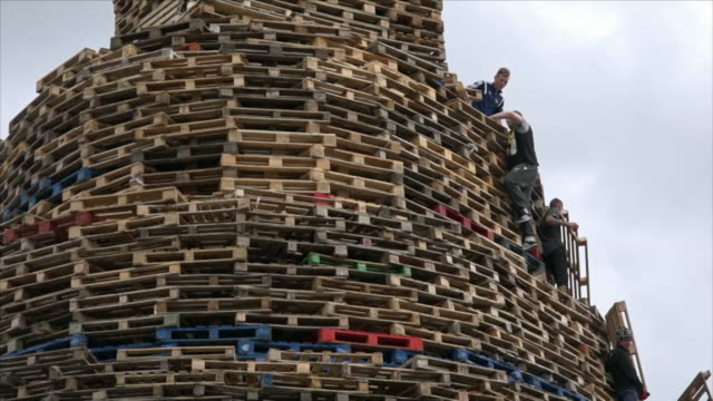 a group of men and boys prepare an enormous pile of wooden pallets for divisive unionist/loyalist bonfire celebrations on the 11th/12th of july 2015, belfast, northern ireland. - belfast stock videos & royalty-free footage