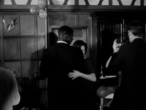 A group of men and women dance the waltz in a wood panelled room 1963