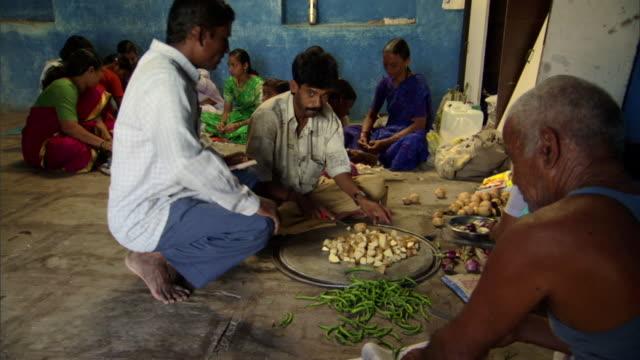 WS Group of men and women seated on ground preparing food for celebration, Pune, Maharashtra, India