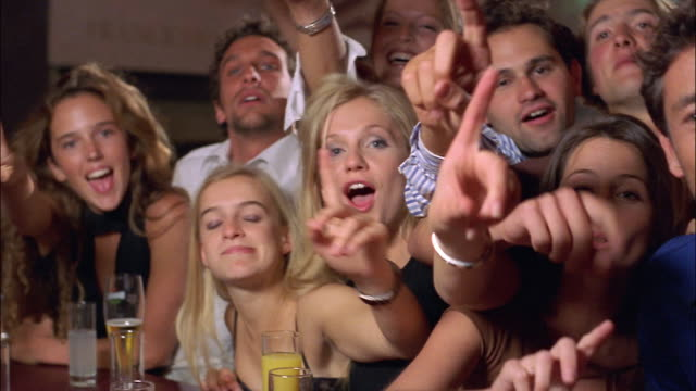 vídeos de stock e filmes b-roll de a group of men and women stand at a crowded bar ordering drinks. - encomendar