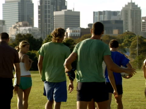 MS, WS, Group of men and women walking on lawn in park after playing soccer, rear view, Sydney, Australia