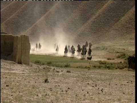 group of men arriving at village on horseback, arid landscape in afghanistan - recreational horseback riding stock videos & royalty-free footage