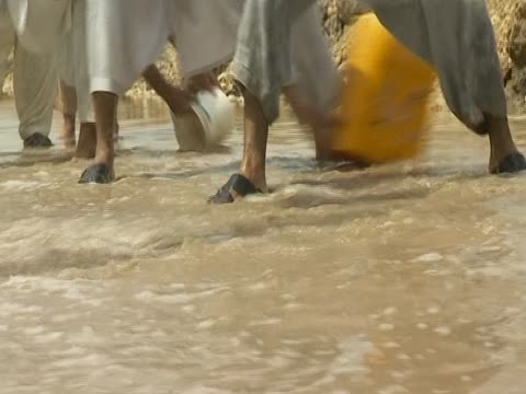 group of men attempt to control floodwaters using buckets following severe rains and flooding in pakistan - 2010 video stock e b–roll