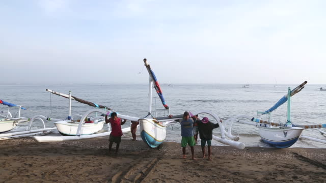group of men carrying their boat onto beach / ubud, bali, indonesia - gemeinsam gehen stock-videos und b-roll-filmmaterial