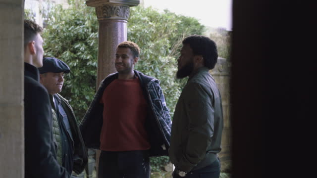Group of men chatting outside a building