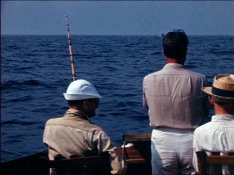 vidéos et rushes de 1941 home movie rear view group of men deep sea fishing off end of boat - seulement des hommes d'âge mûr