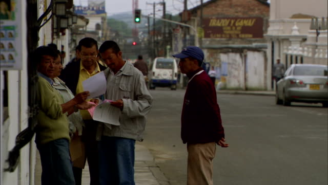 a group of men discuss pamphlets as they stand on a sidewalk - pamphlet stock videos & royalty-free footage