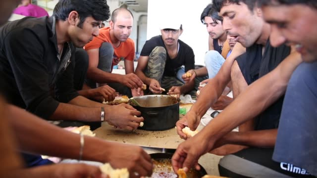 Group of men eat in the grounds of an abandoned hotel that has given refuge to many migrant families on August 29 2015 in Kos Greece Migrants from...