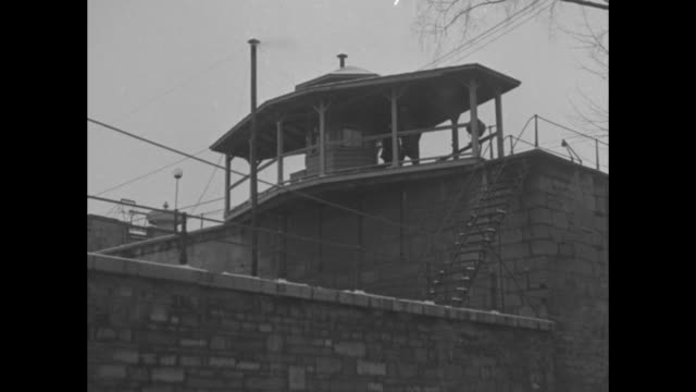group of men gathered outside closed prison gate / troopers on top of prison wall / shot from below of men standing next to guard booth on top of... - prison riot stock videos & royalty-free footage