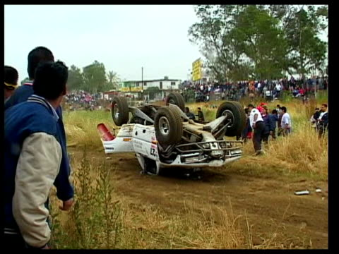 vídeos de stock e filmes b-roll de ms, zo, zi, cu, group of men gathering around crashed race car with fuel leaking on ground, then turning it over back on its wheels, ensenada, mexico - península de baixa califórnia