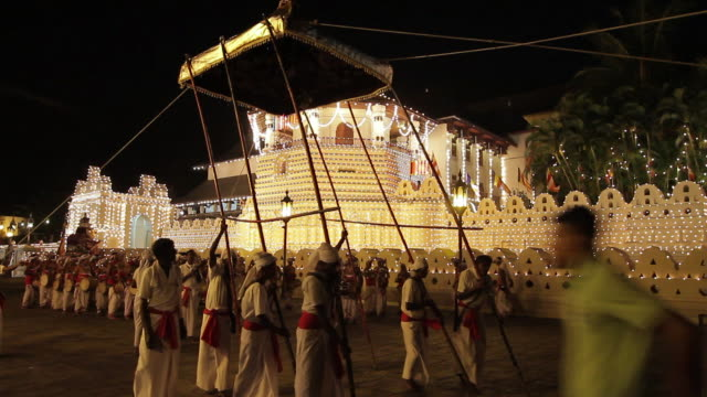 stockvideo's en b-roll-footage met ms zo group of men hoist 'sacred canopy' in buddhist festival or procession 'esala perahera' in front of 'temple of tooth' audio / kandy, central province, sri lanka - sri lankaanse cultuur