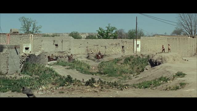 stockvideo's en b-roll-footage met ws pan group of men horseback riding on dirt road outside city walls - letterbox format