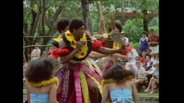 vídeos de stock e filmes b-roll de group of men in figi perform a 'spear dance' for tourists while carrying spears, hand fans and dressed in traditional clothing and standing on a... - cultura polinésia