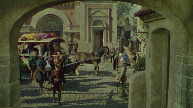 ms group of men in medieval town carrying body covered with white sheet and horses pulling wagons in background - courtyard stock videos & royalty-free footage