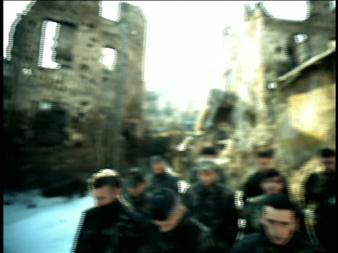 vidéos et rushes de soft focus pan group of men in military fatigues standing among ruins bowing heads / sarajevo - guerre