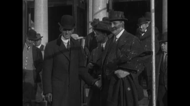 group of men in suits and hats on steps of building / henry ford in overcoat & hat with wife clara - ヘンリー・フォード点の映像素材/bロール