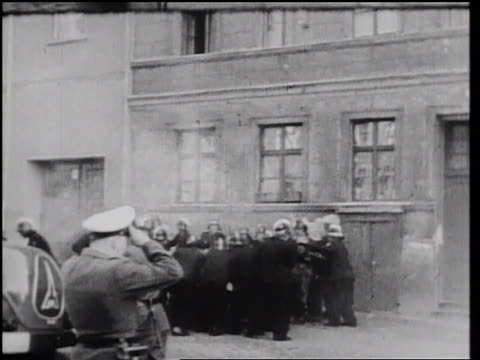 stockvideo's en b-roll-footage met b/w 1961 group of men in uniforms standing near building at border of east west berlin / newsreel - ontsnappen