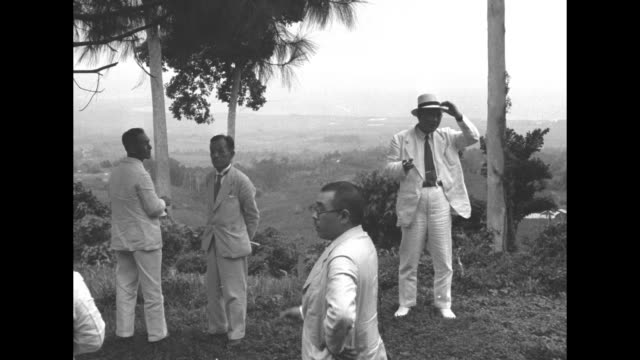 group of men in white standing atop a hill overlooking a valley with one bowing to japanese adm. kichisaburo nomura, who is in the philippines to... - フィリピン人点の映像素材/bロール